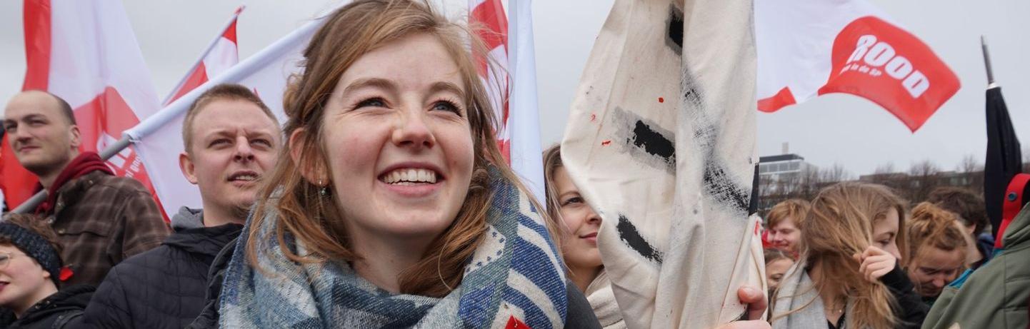 Lachende student met vlag in de hand bij een demonstratie
